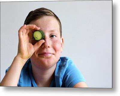 Boy Holding Cucumber Over Eye Metal Print by Gombert, Sigrid