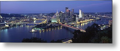 Buildings Along A River Lit Up At Dusk Metal Print by Panoramic Images