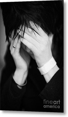 Close Up Of Young Dark Haired Teenage Man Sitting With His Head In His Hands Hiding His Face Staring Metal Print by Joe Fox