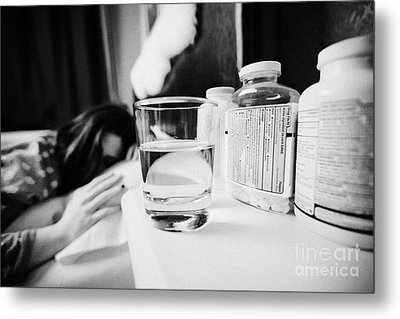 Glass Of Water And Bottles Of Pills On Bedside Table Of Early Twenties Woman In Bed In A Bedroom Metal Print by Joe Fox