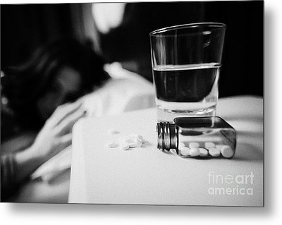 Glass Of Water And Bottles Of Sleeping Pills On Bedside Table Of Early Twenties Woman In Bed In A Be Metal Print by Joe Fox