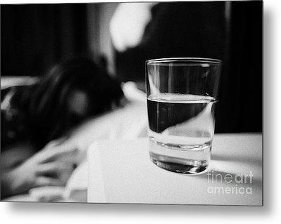 Glass Of Water On Bedside Table Of Early Twenties Woman In Bed In A Bedroom Metal Print by Joe Fox