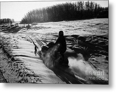 man on snowmobile crossing frozen fields in rural Forget canada Metal Print by Joe Fox