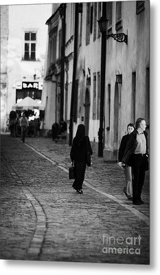 nun with briefcase walking up cobblestone street Kanonicza past tourists in old town krakow Metal Print by Joe Fox