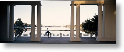 Person Stretching Near Colonnade, Lake Metal Print by Panoramic Images