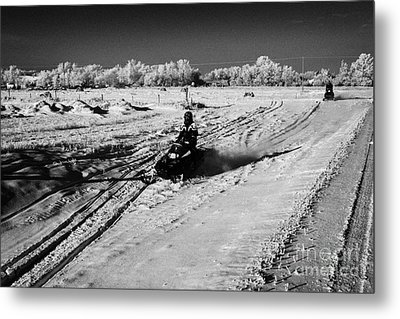 two men on snowmobiles crossing frozen fields in rural Forget Saskatchewan Canada Metal Print by Joe Fox