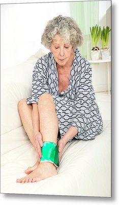 Woman With A Cold Compress On Ankle Metal Print