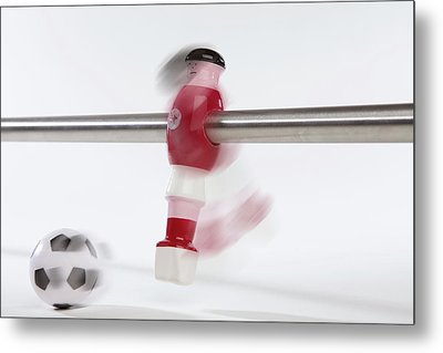 A Foosball Figurine Kicking A Soccer Ball, Blurred Motion Metal Print by Caspar Benson