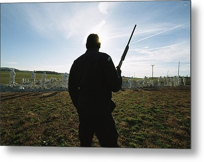 An Armed Guard Watches Over Inmates Metal Print by Bill Curtsinger