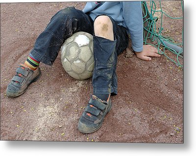 Boy With Soccer Ball Sitting On Dirty Field Metal Print by Matthias Hauser