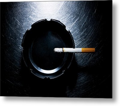 Lit Cigarette And Ashtray On Stainless Steel. Metal Print by Ballyscanlon