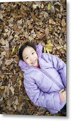 Smiling Girl Lying On Autumn Leaves Metal Print by Ian Boddy