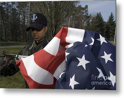 Soldier Unfurls A New Flag For Posting Metal Print by Stocktrek Images