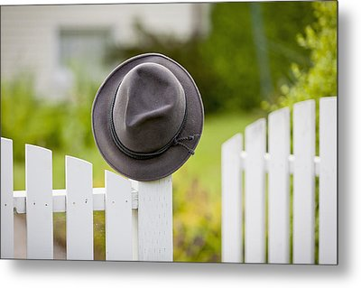 A Hat Hanging On The Post Of A White Metal Print by Lorna Rande