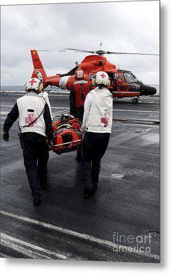 Personnel Carry An Injured Sailor Metal Print by Stocktrek Images