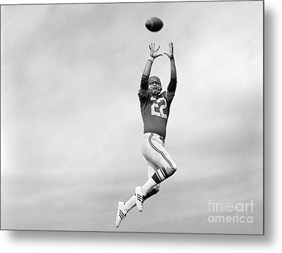 Player Jumping To Catch Football Metal Print by H. Armstrong Roberts/ClassicStock