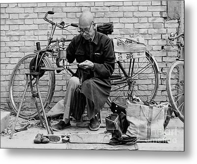 Metal Print featuring the photograph The Shoe Mender by Nigel Fletcher-Jones