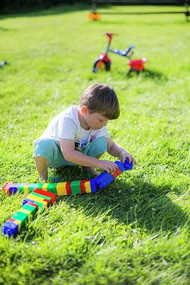 Boy Playing With Plastic Bricks Poster