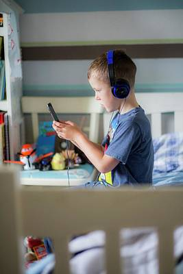 Boy Wearing Headphones Using Device Poster