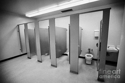 cubicle toilet stalls in womens bathroom in a High school canada north america Poster