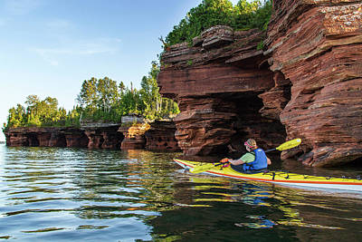 Kayaker Exploring The Sea Caves Poster by Chuck Haney