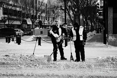 public workers clearing snow and ice off the sidewalks in downtown Saskatoon Saskatchewan Canada Poster by Joe Fox