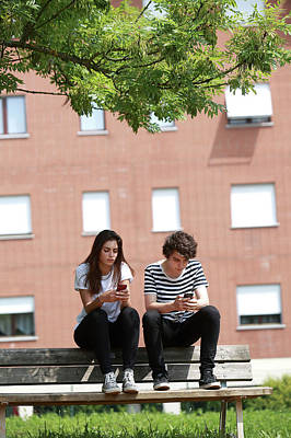 Teenage Couple Using Smart Phones Poster by Mauro Fermariello