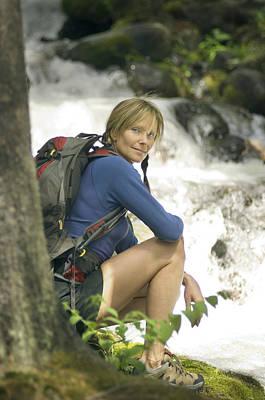 Woman Hiking Along A Creek Poster