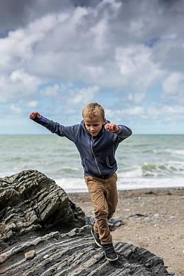 Young Boy Playing On Rocks On Beach Poster