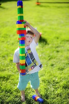 Boy Playing With Plastic Bricks Poster by Samuel Ashfield