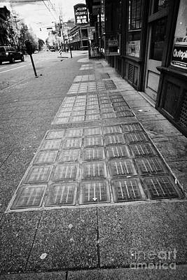 glass blocks in the sidewalk to light basement of the sam kee building in Vancouver BC Canada Poster