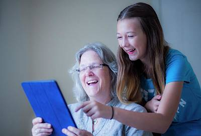 Girl And Grandmother Using Tablet Poster by Samuel Ashfield