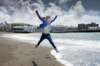 Girl Leaping On Beach Poster