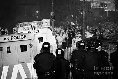 Psni Riot Officers Face Rioters Mob On Crumlin Road At Ardoyne Shops Belfast 12th July Poster by Joe Fox