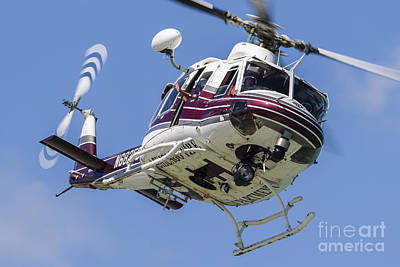 A Bell 412 Helicopter Flies Poster by Rob Edgcumbe