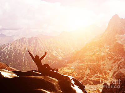 A Happy Man Sitting On The Peak Of A Mountain With Hands Raised At Sunset Poster