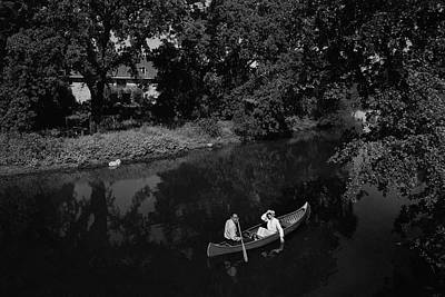 A Man And Woman In A Canoe On A Lake Poster by Roger Sturtevant