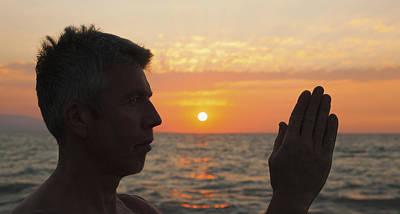 A Man In Prayer Or Yoga Pose As The Sun Poster by Debra Brash