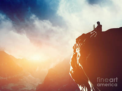 A Man Working On Laptop Sitting On The Peak Of A Mountain At Sunset Poster