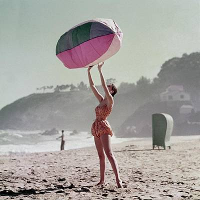 A Model Wearing A Bathing Suit Holding Up An Poster
