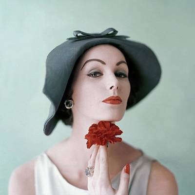 A Model Wearing A Hat And Holding A Flower Poster by Karen Radkai