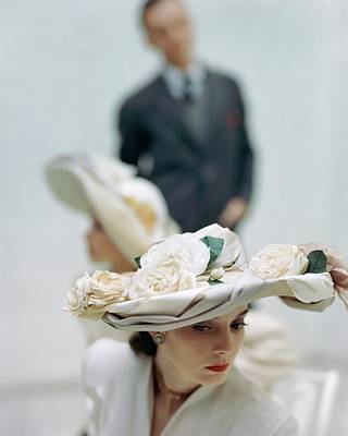 A Model Wearing A Hat Decorated With Flowers Poster