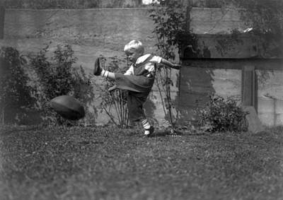 A Small Boy Kicking Football Poster by Underwood Archives