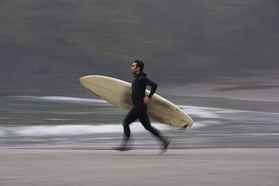 A Surfer Running To The Water With His Poster