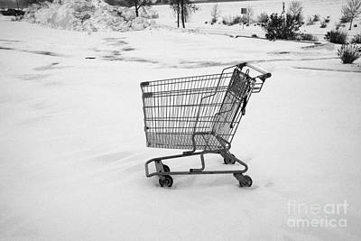 abandoned shopping cart in snow covered supermarket parking lot Saskatoon Saskatchewan Canada Poster by Joe Fox