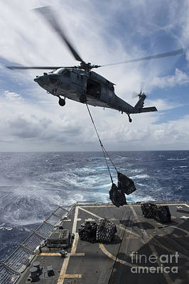 An Sh-60s Sea Hawk Delivers Supplies Poster
