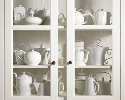 Assorted Tea And Coffee Pots In A Glass Cupboard Poster by Sivan Lewin