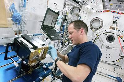 Astronaut Cleaning Iss Lab Equipment Poster by Nasa