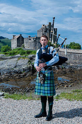 Bagpipe Player At Famous Eilean Donan Castle In The Highlands Of Scotland Poster by Frank Gaertner