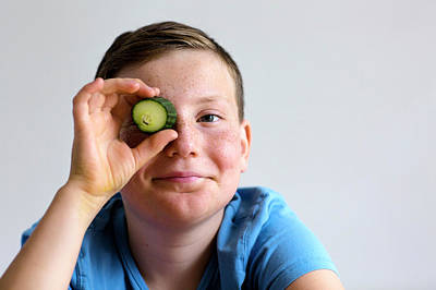 Boy Holding Cucumber Over Eye Poster